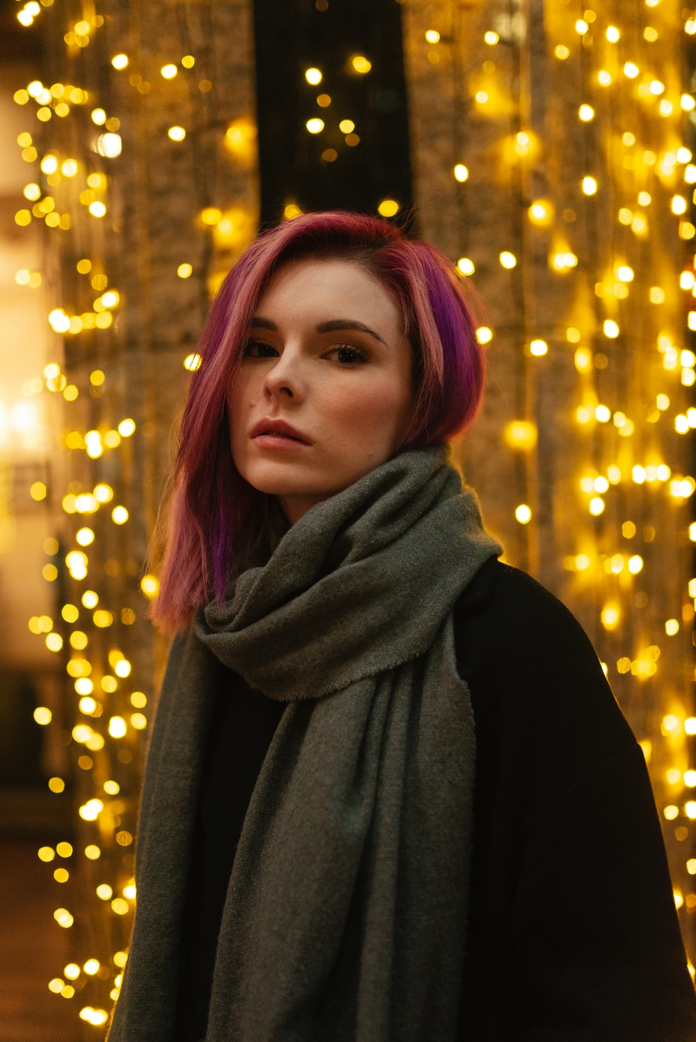 woman in black scarf standing near yellow lights
