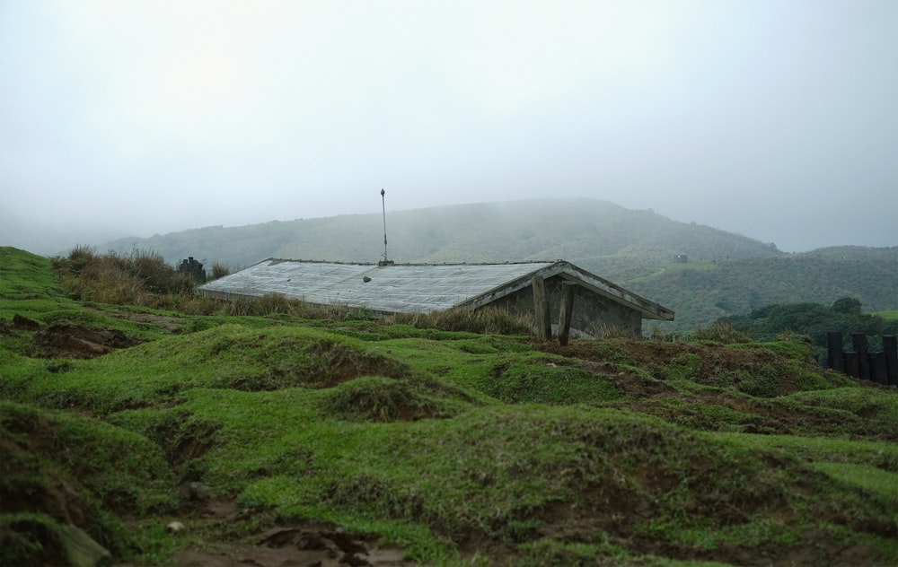 brown wooden house on green grass field near mountain under white sky during daytime
