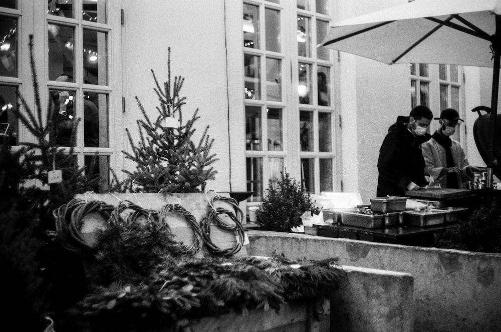 grayscale photo of man in black jacket standing near window