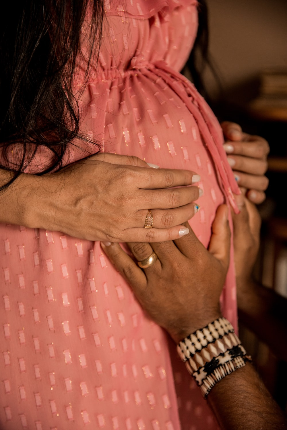 woman in pink and white polka dot dress wearing gold ring