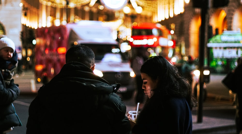 man and woman standing in the street during night time