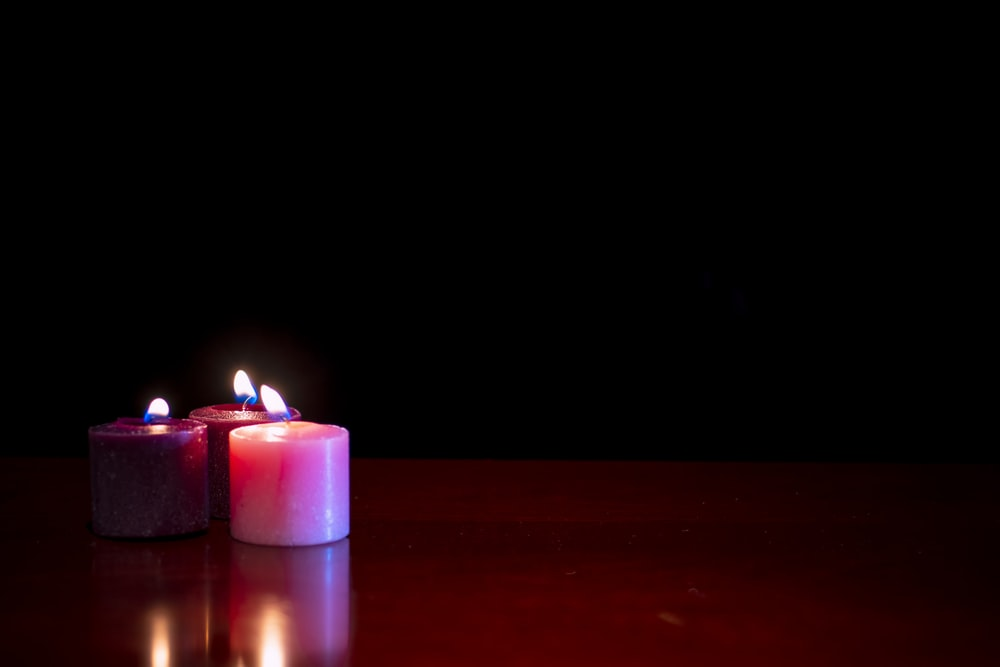 purple lighted candle on brown wooden table