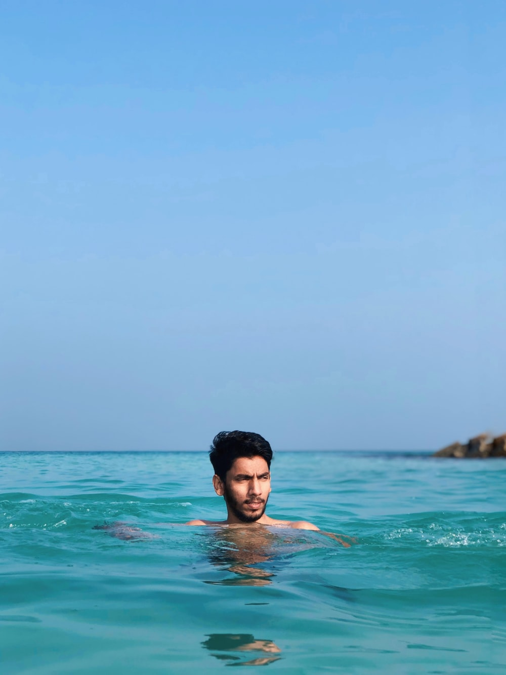 man in blue swimming trunks in sea during daytime