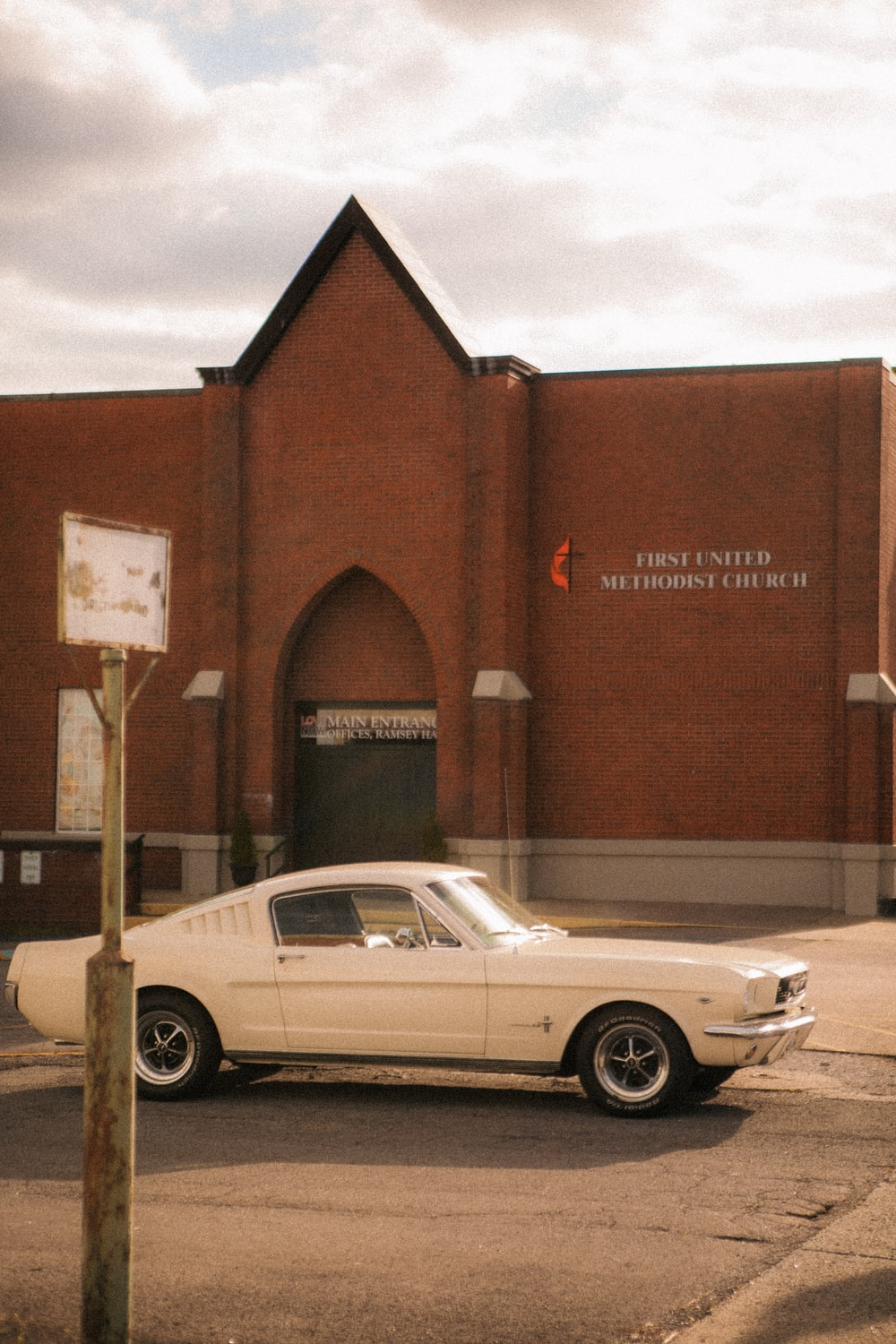 white coupe parked beside brown building