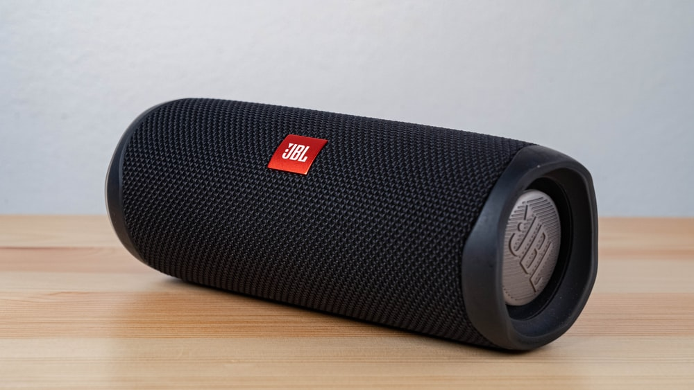 black jbl portable speaker on brown wooden table