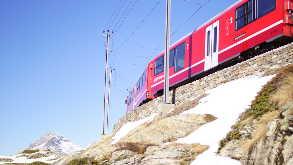red and white train on rail tracks during daytime