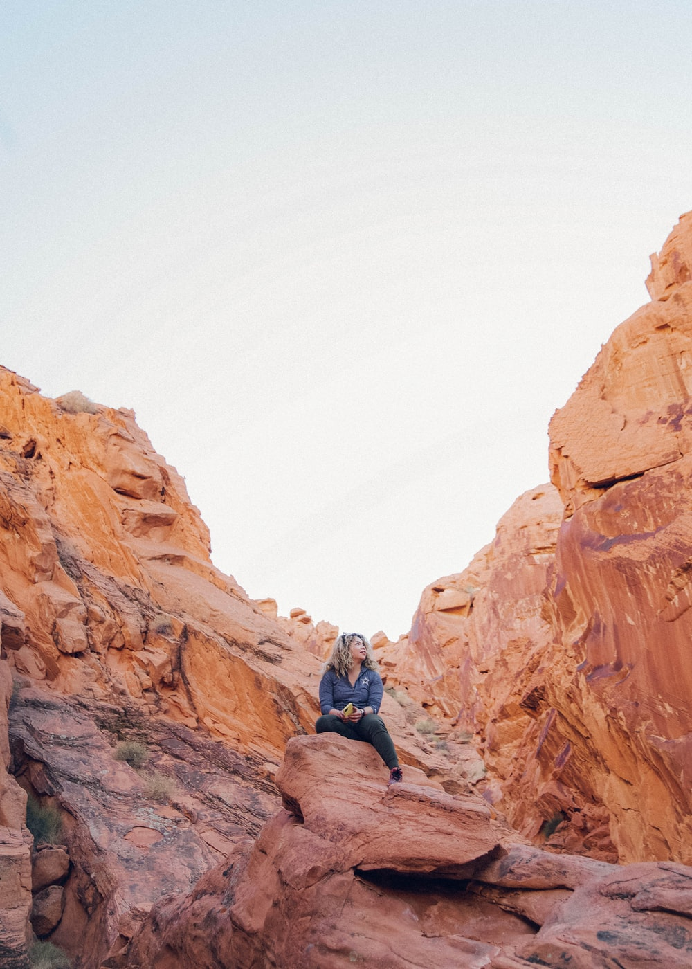 man in blue jacket and black pants sitting on brown rock formation during daytime