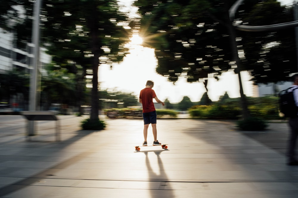 man in red t-shirt and blue denim jeans playing skateboard during daytime