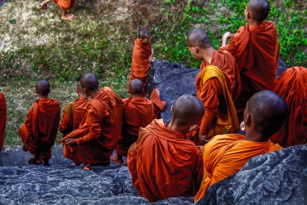 boys in orange robe sitting on gray rock during daytime