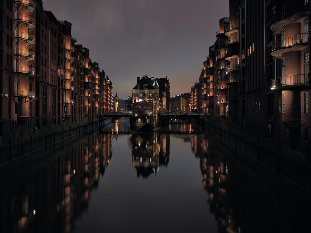 body of water between high rise buildings during night time