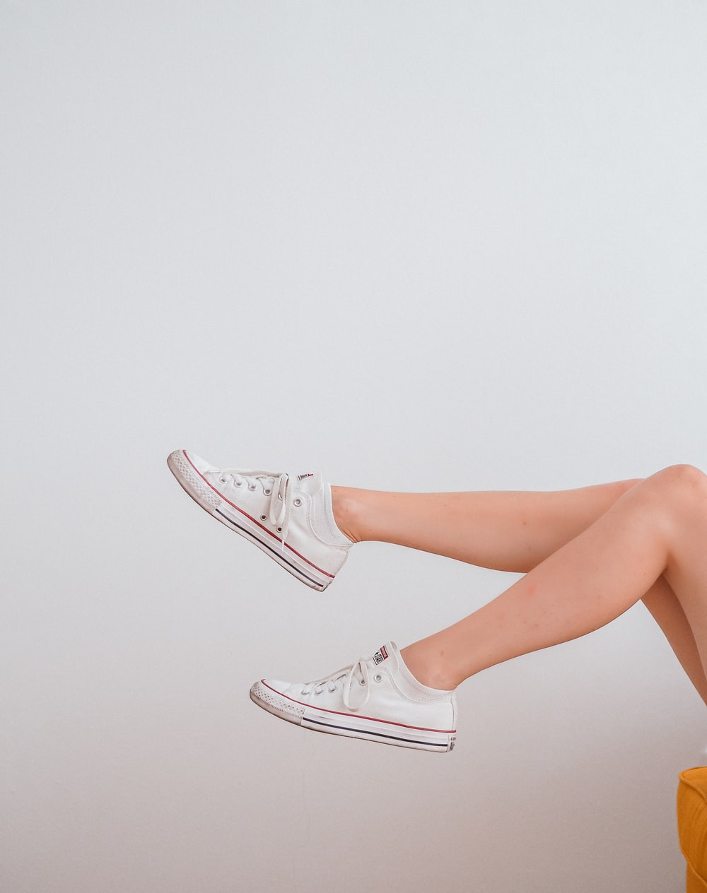 woman in white low top sneakers