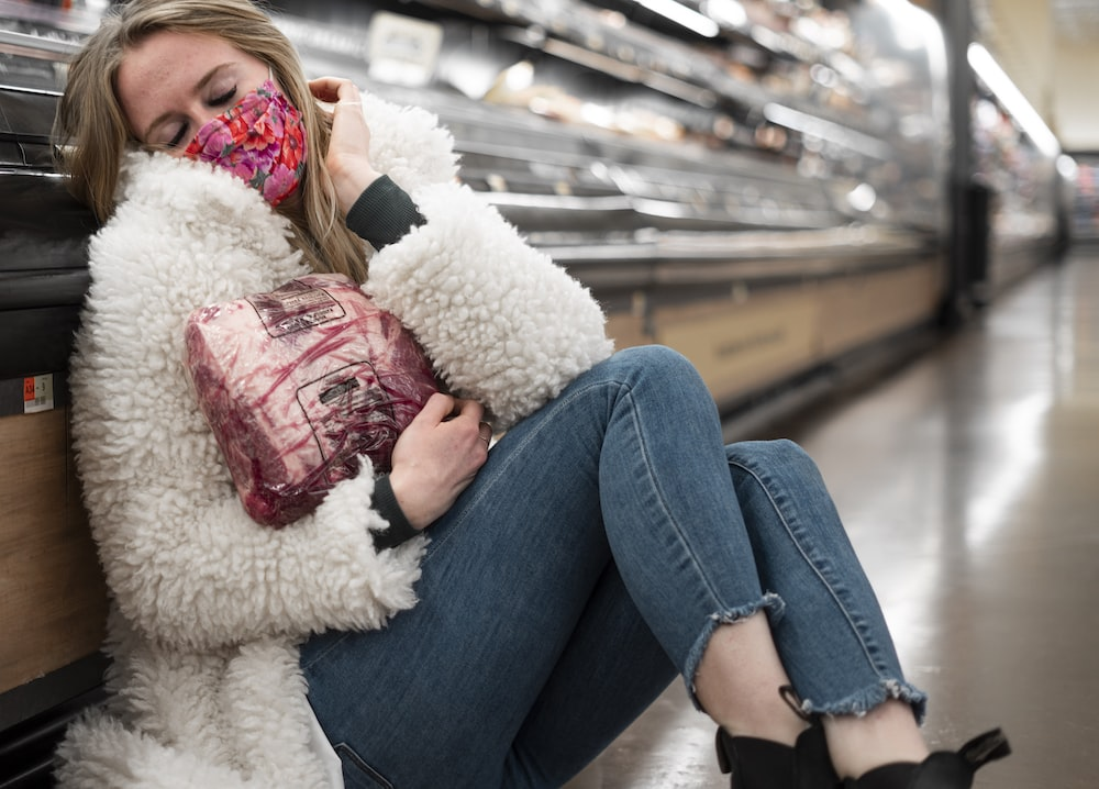 woman in blue denim jeans lying on white fur textile