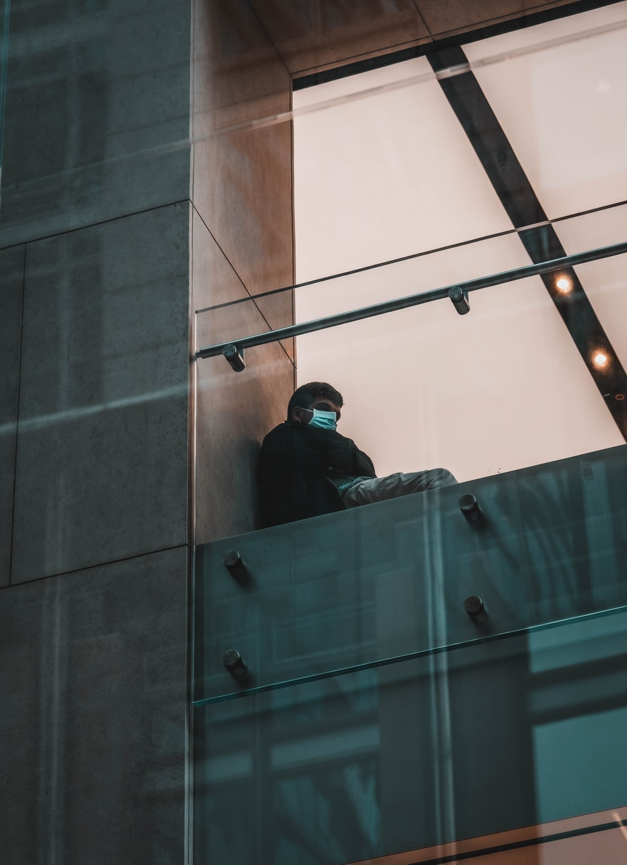 man in black jacket standing beside glass wall