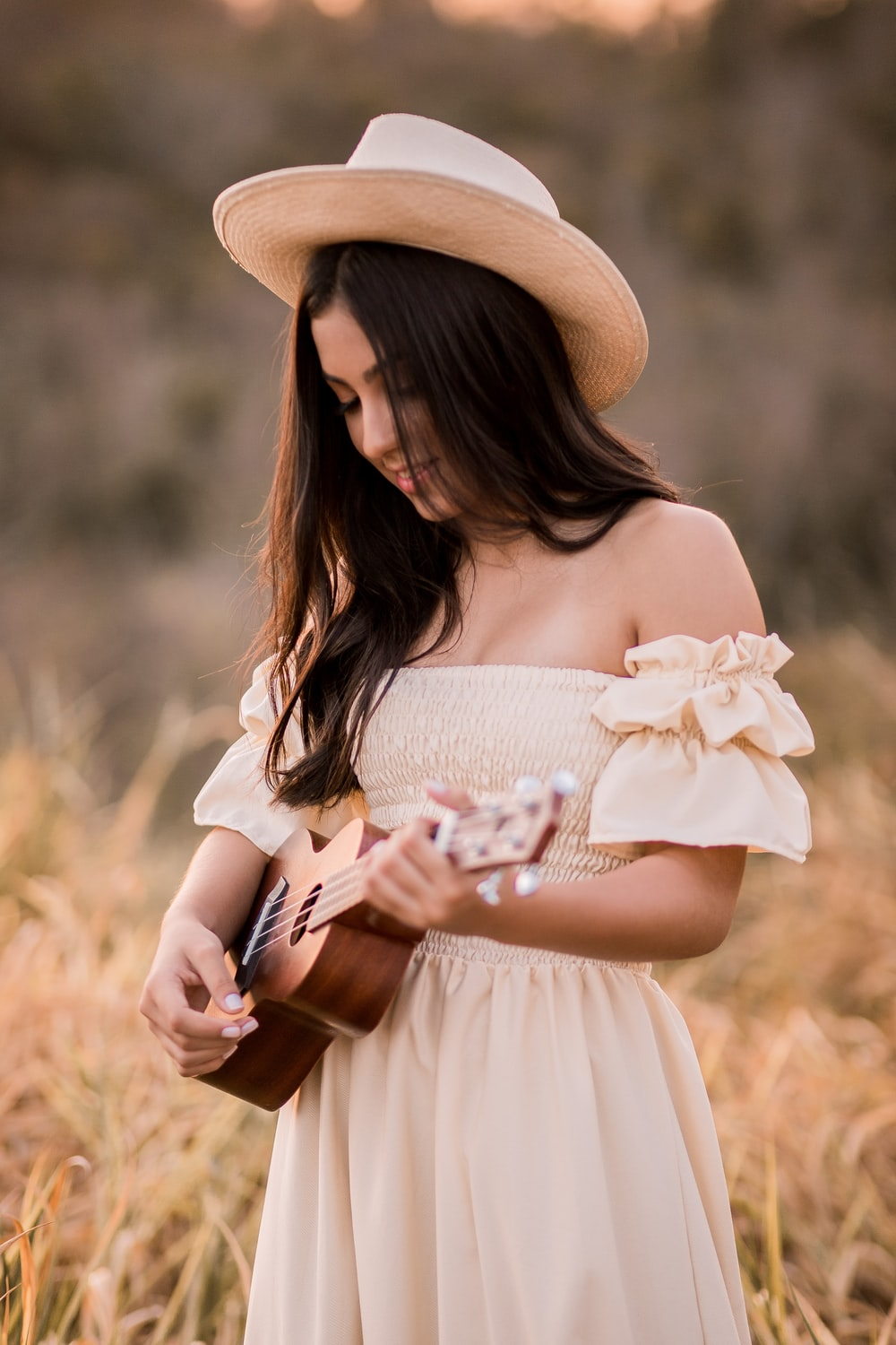 woman in white dress wearing brown sun hat holding white flower bouquet