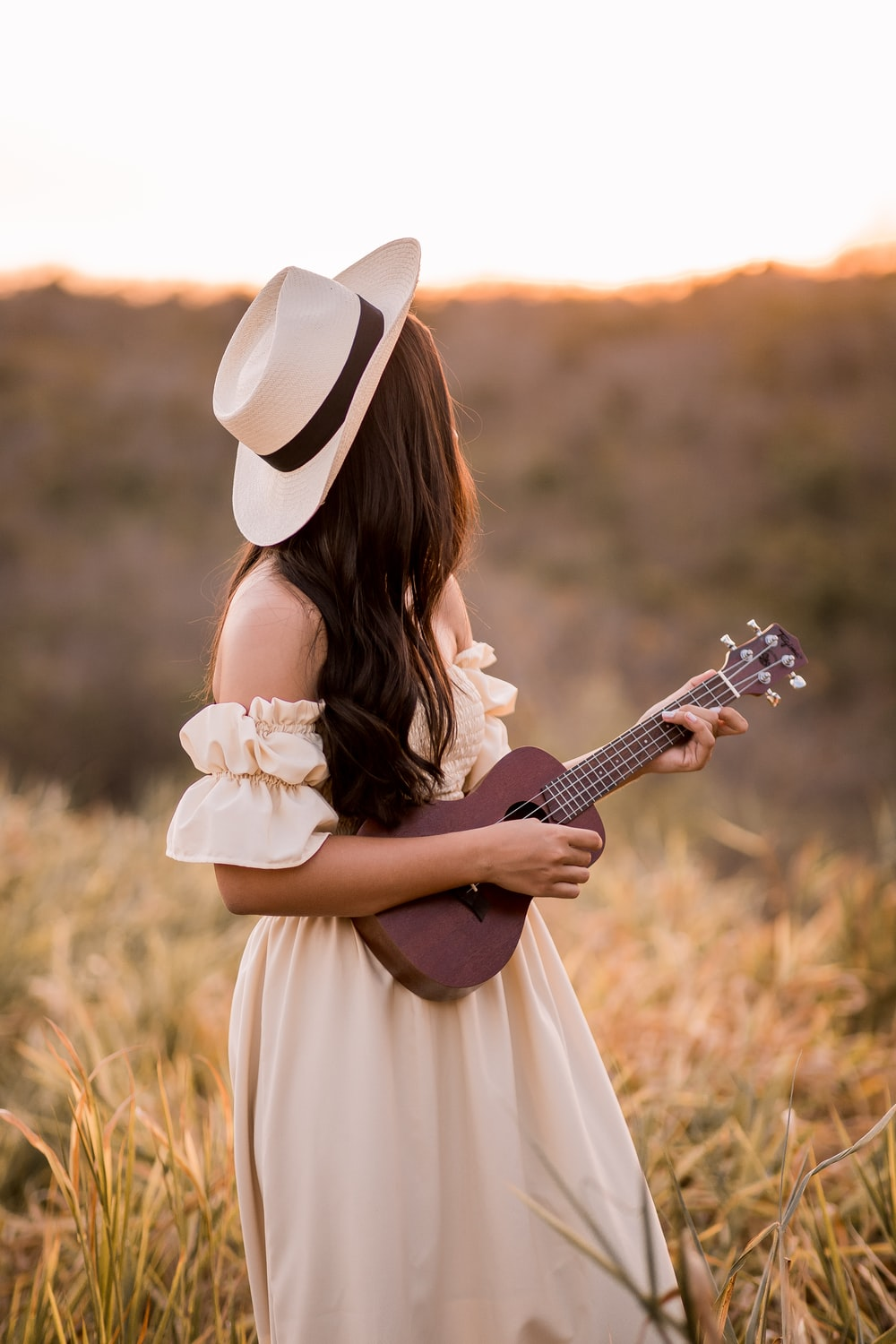 woman in white dress playing acoustic guitar
