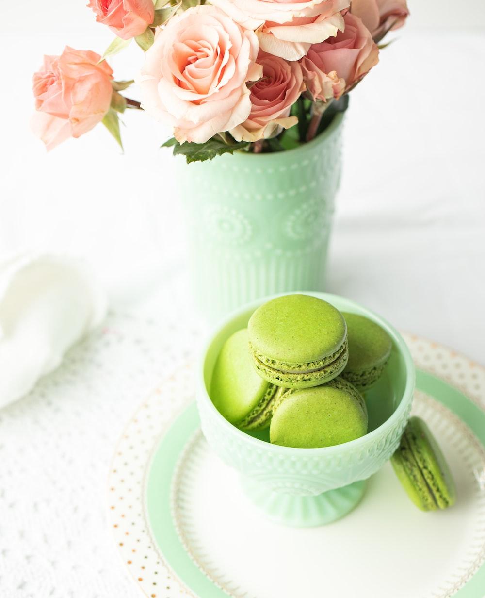 green egg on white ceramic bowl beside pink flowers
