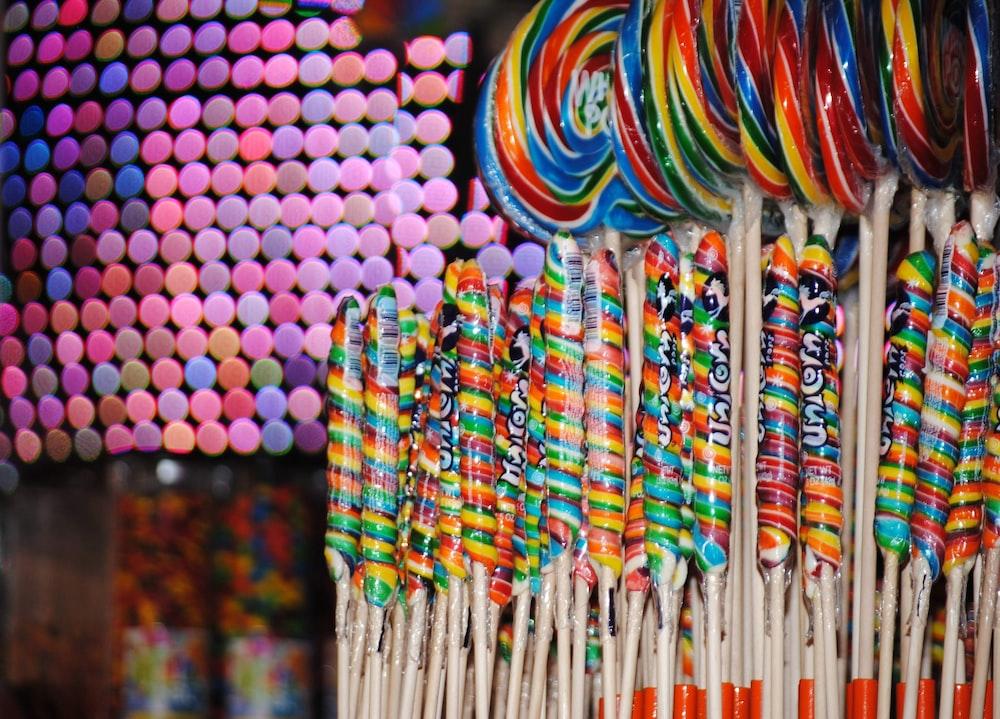 multi colored round lollipop on white paper