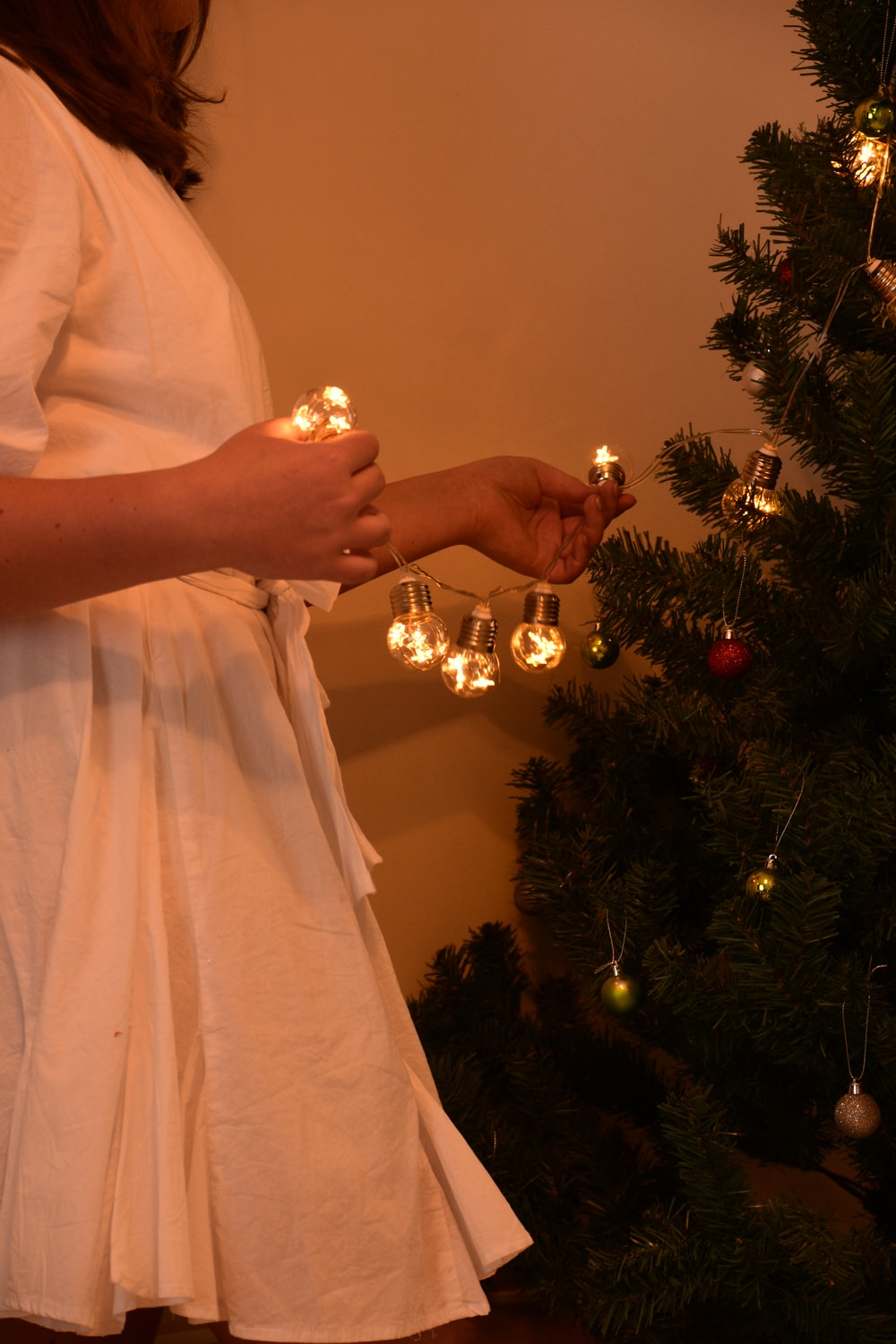 person holding gold ornament near christmas tree