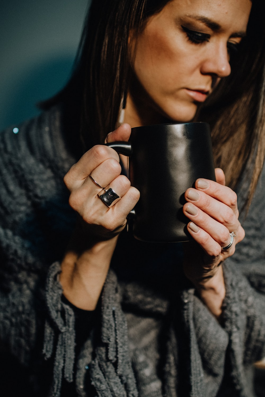 woman in black and white sweater holding black ceramic mug