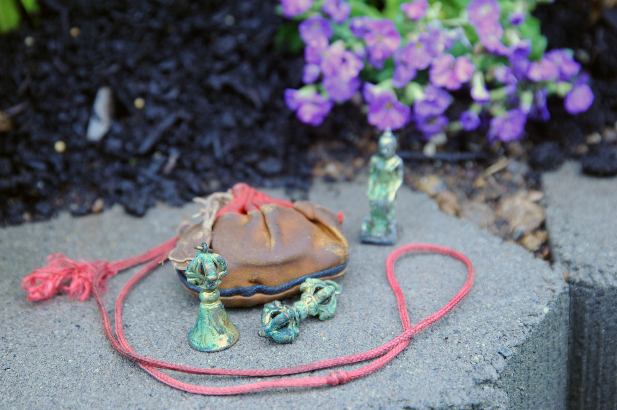 Contents from an old Tibetan Buddhist Trungwas, or protection amulets, dorje, bell, a statue of Maitreya, the Buddha of the future seated, blessing cord, bag, Garden for the Buddha, Seattle, Washington, USA