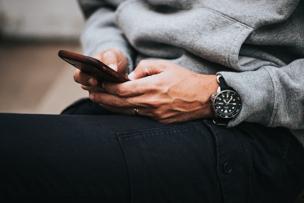 person in gray sweater wearing black and silver chronograph watch