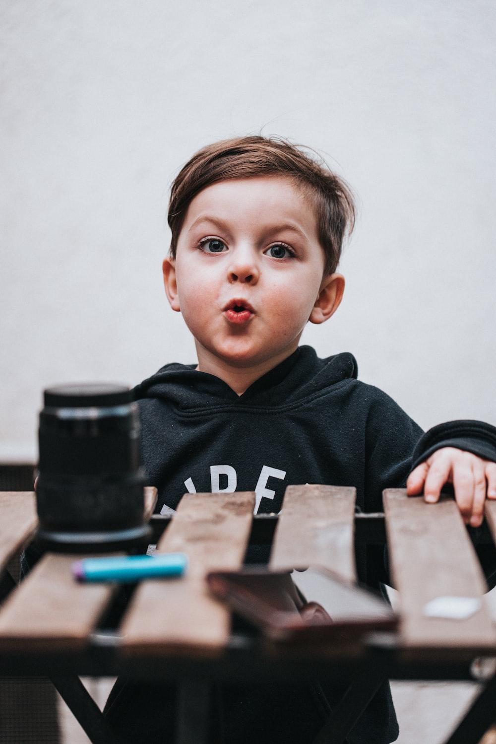 boy in black hoodie sitting beside black dslr camera
