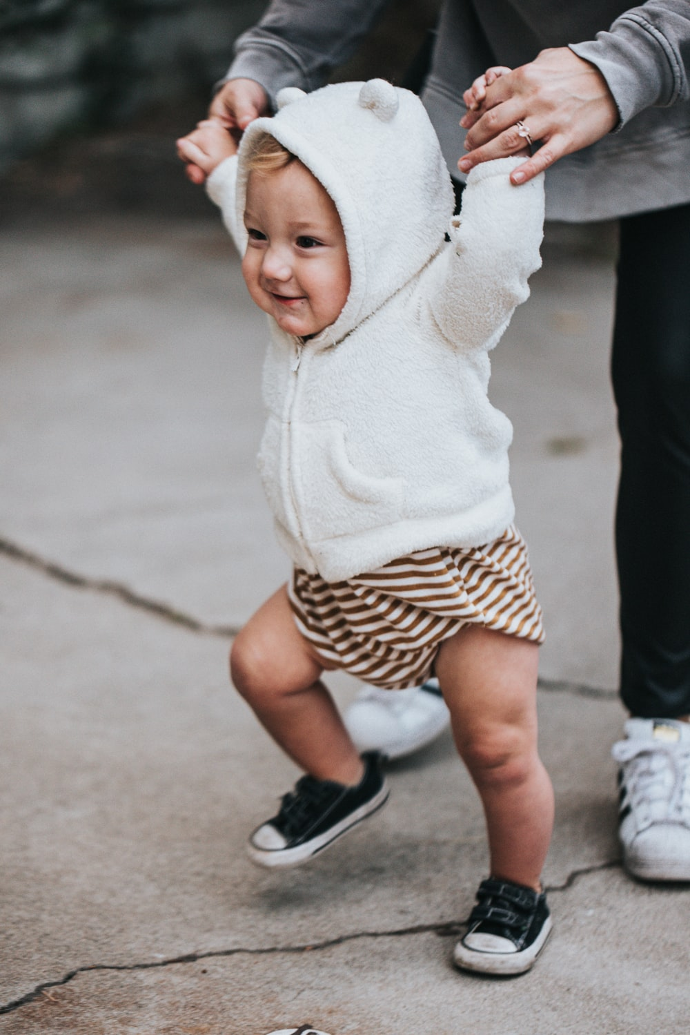 baby in white knit sweater and black and white polka dot shorts