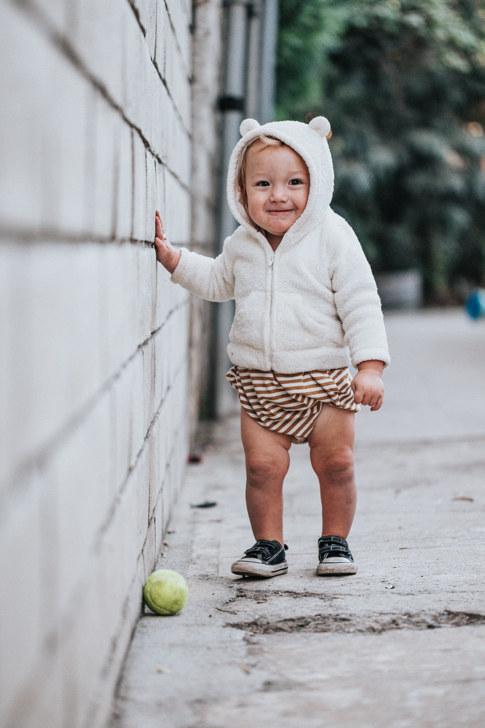 girl in white hoodie and brown and white polka dots skirt holding green tennis ball