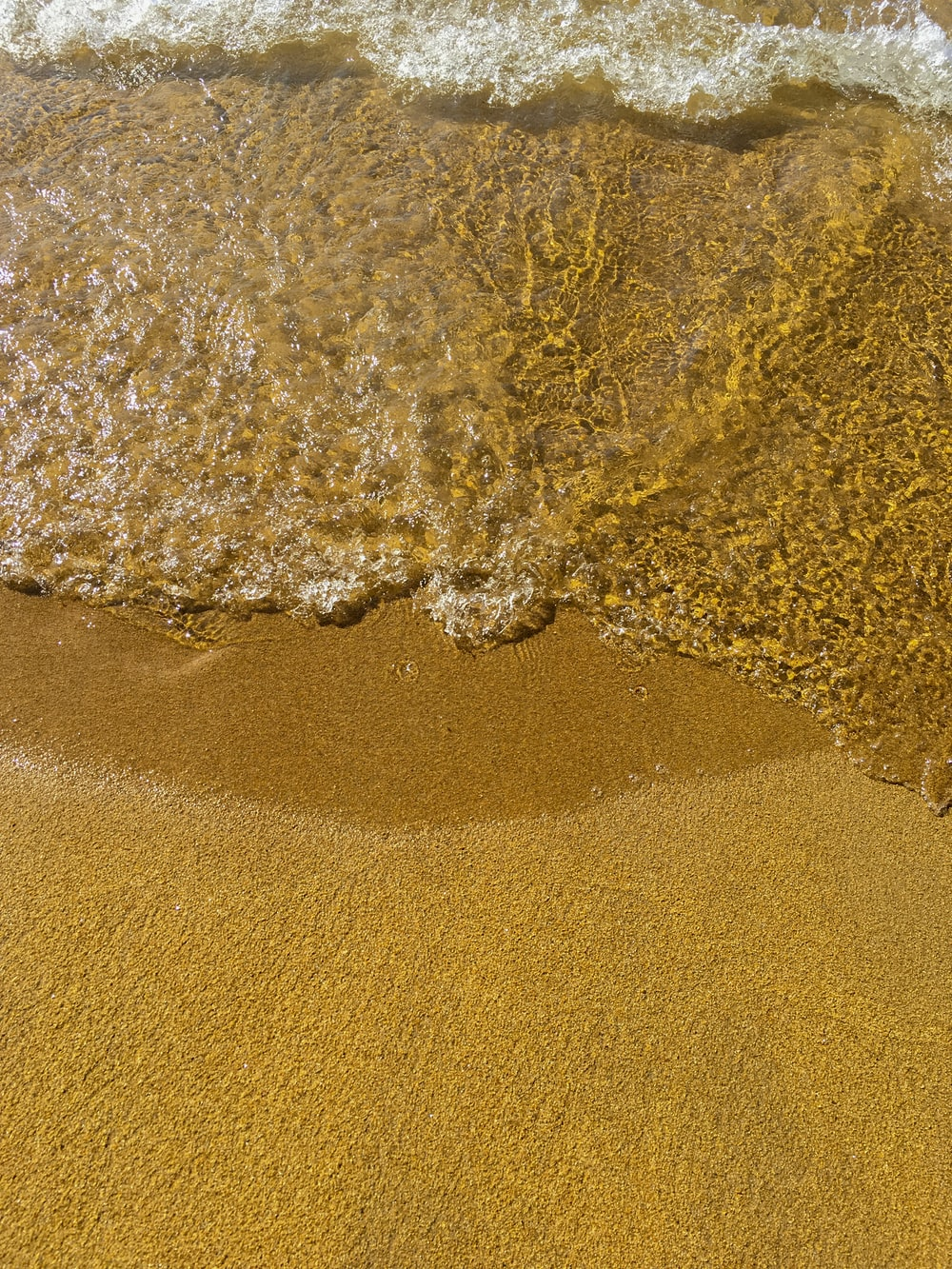 brown sand and body of water