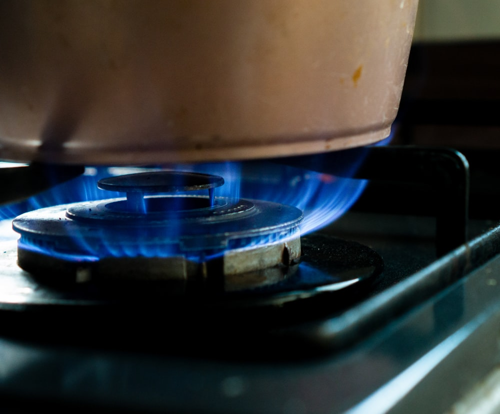 white plastic container on black gas stove