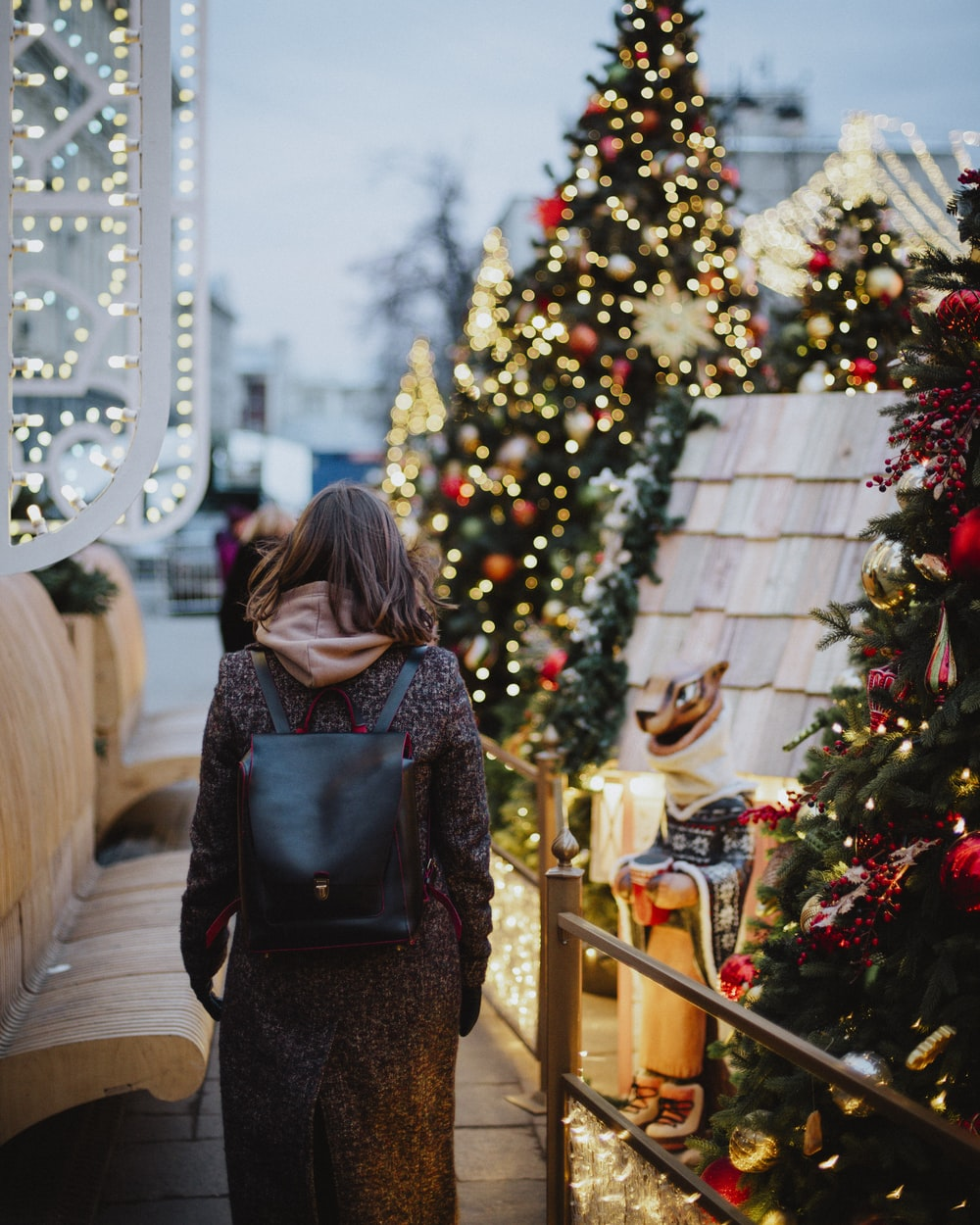 woman in black and brown backpack standing near green christmas tree