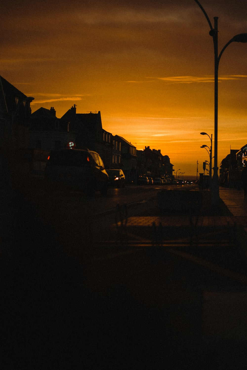 cars parked on side of the road during sunset