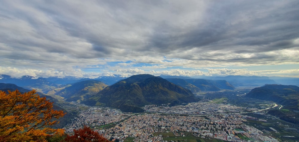 aerial view of city near mountain under cloudy sky during daytime