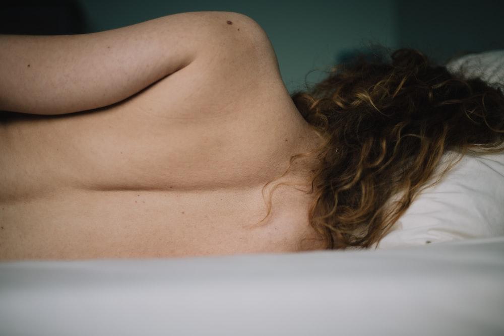 topless woman lying on white bathtub