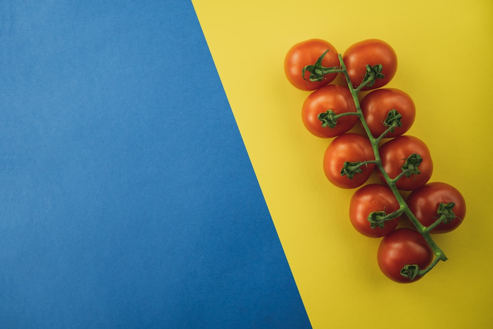 red round fruits on blue and yellow surface