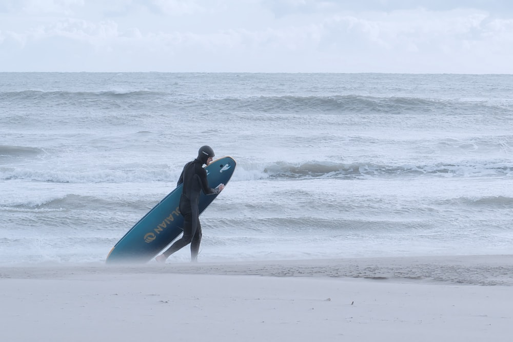 man in blue wetsuit holding blue surfboard walking on beach during daytime