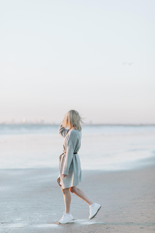 girl in white dress standing on beach during daytime