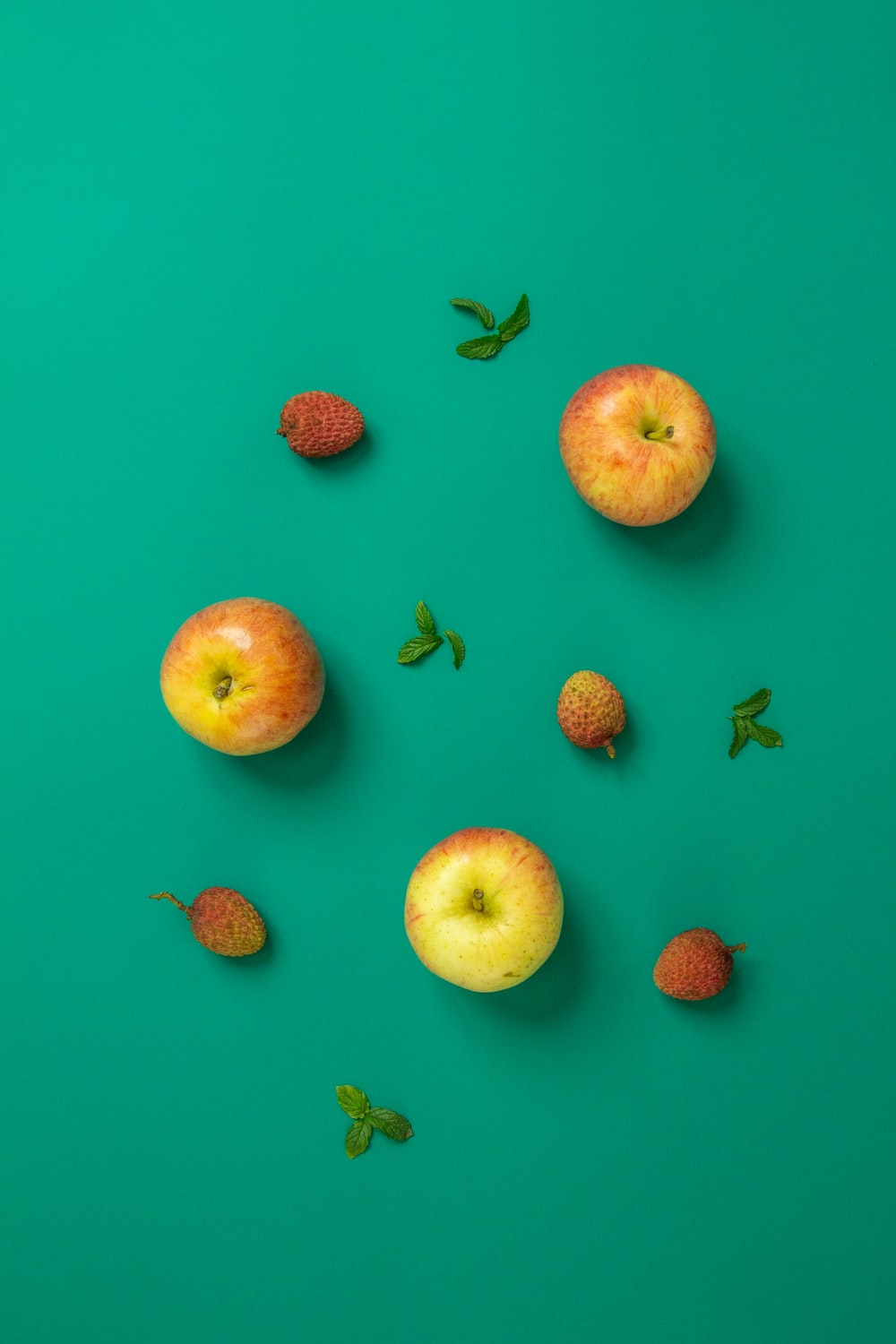 sliced apple and strawberries on pink surface