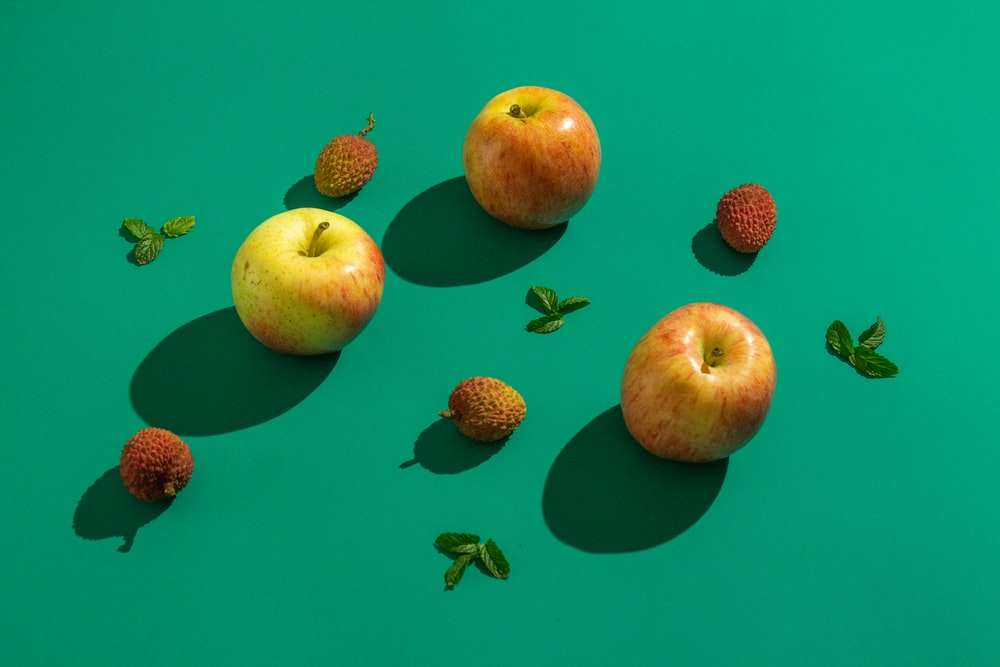 red and green apples on blue surface