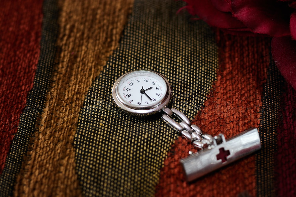 silver pocket watch on brown textile
