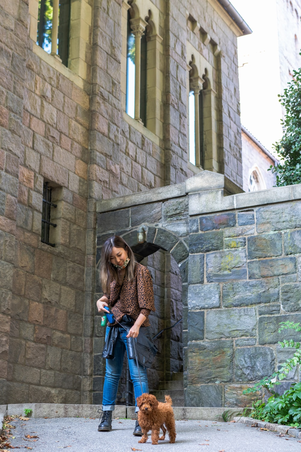 woman in brown and black leopard print long sleeve shirt standing beside brown brick wall during