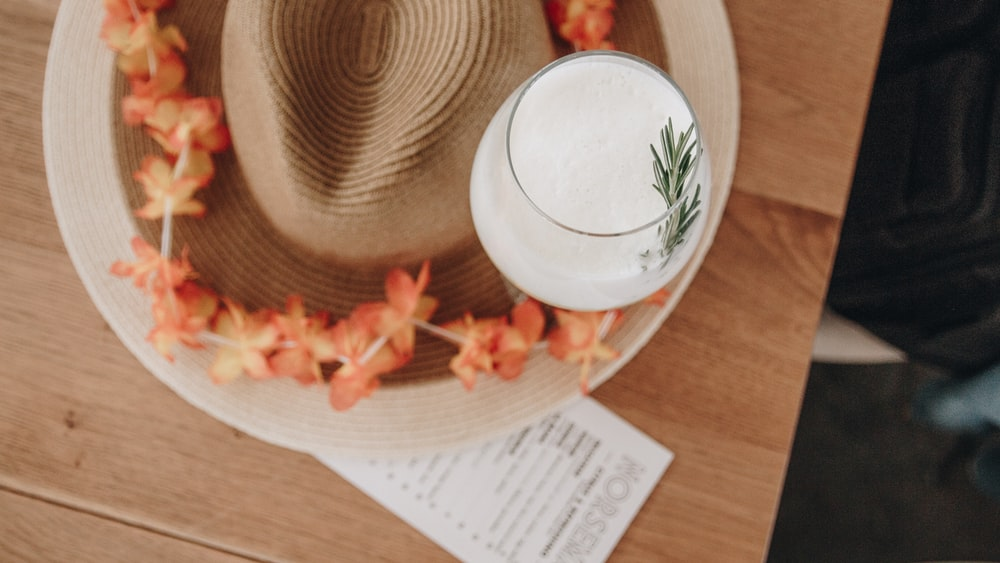 white fedora hat on brown wooden table