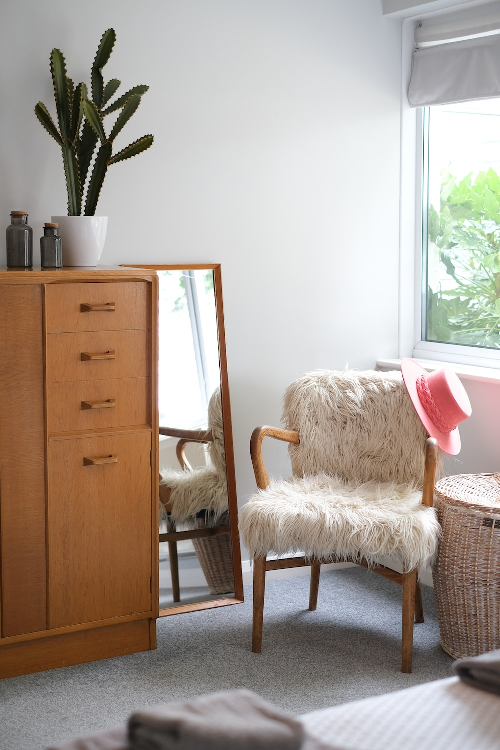 white and brown wooden chair beside brown wooden cabinet