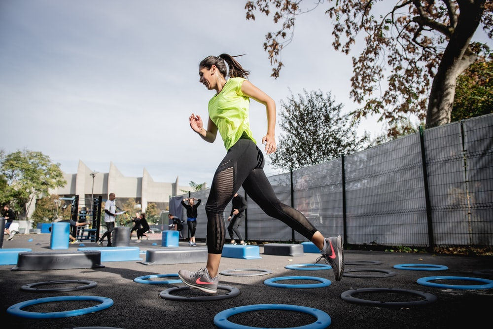woman in green tank top and black leggings doing yoga on blue round trampoline