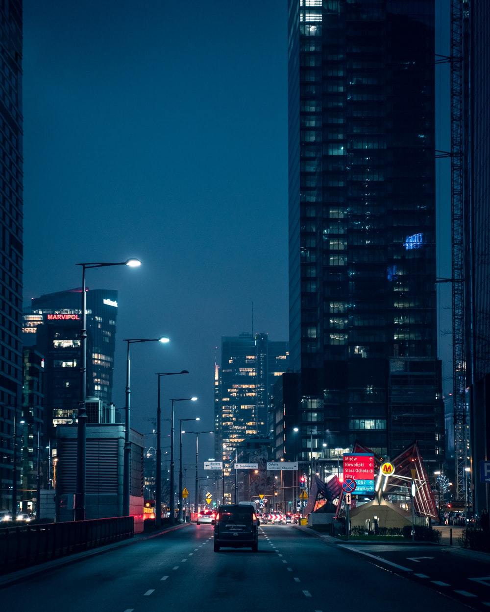 cars on road near high rise buildings during night time
