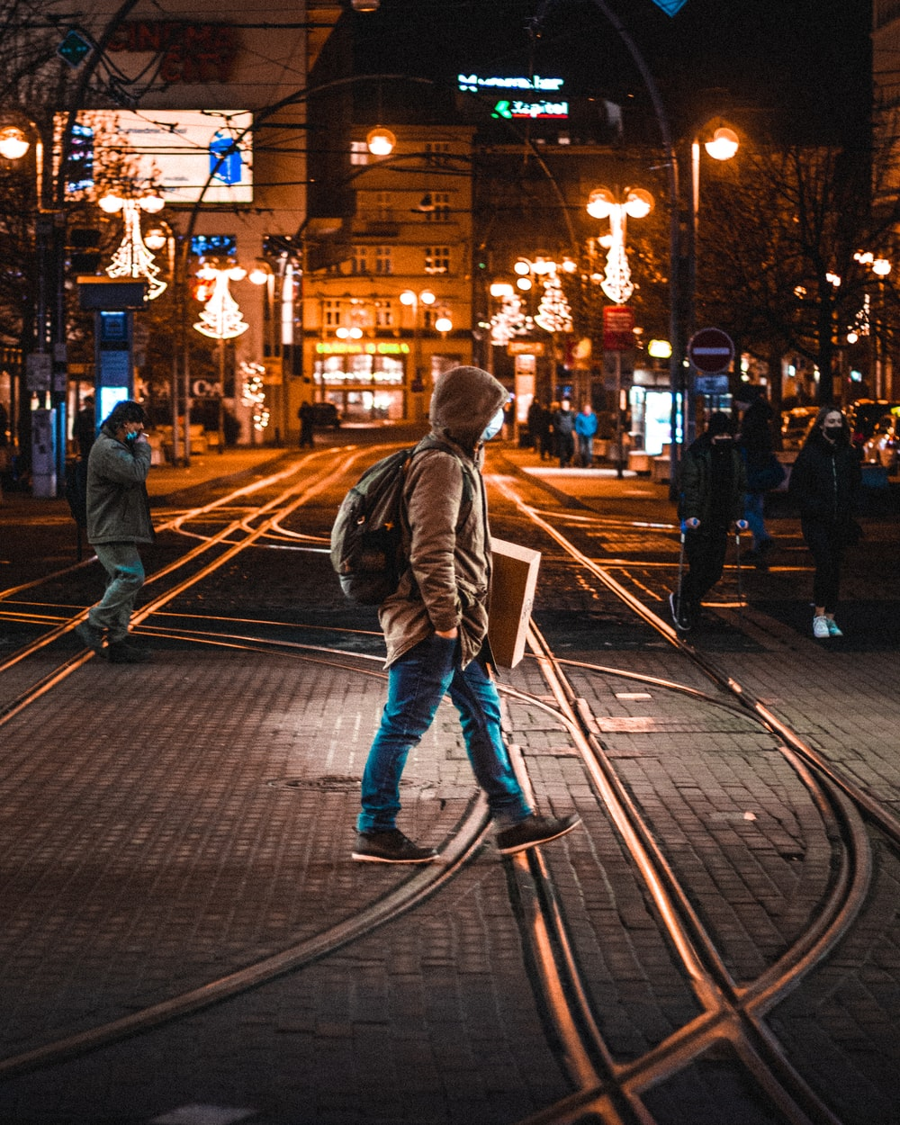 woman in gray jacket walking on sidewalk during night time