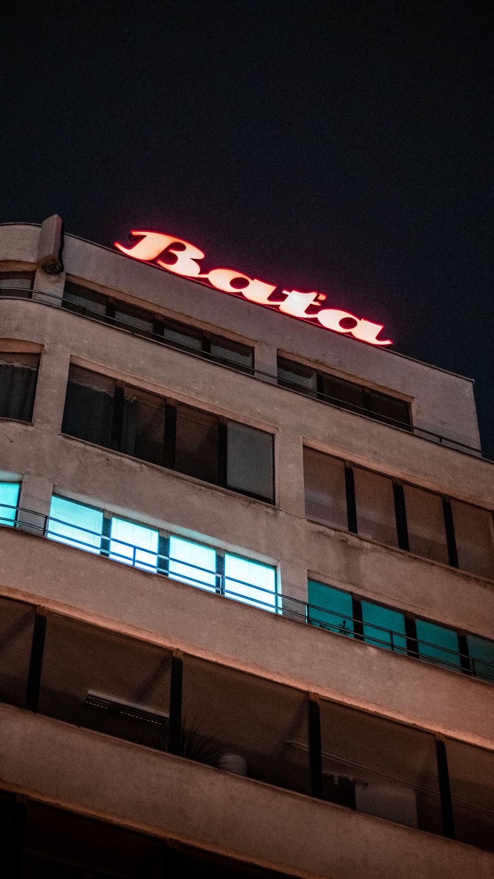 brown concrete building with red and blue neon light signage