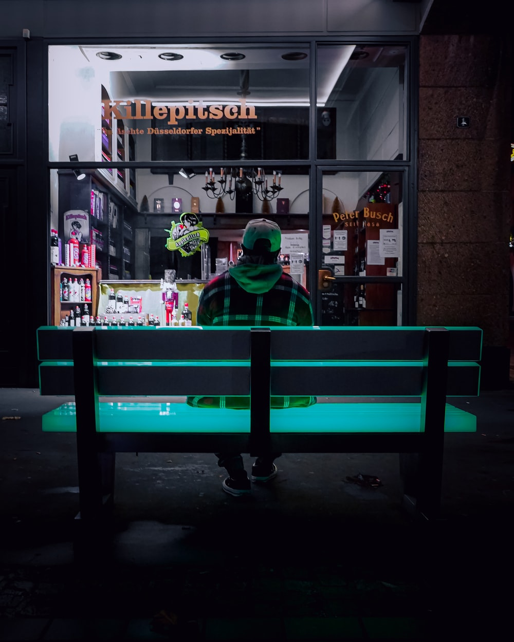 man in green jacket sitting on red bench