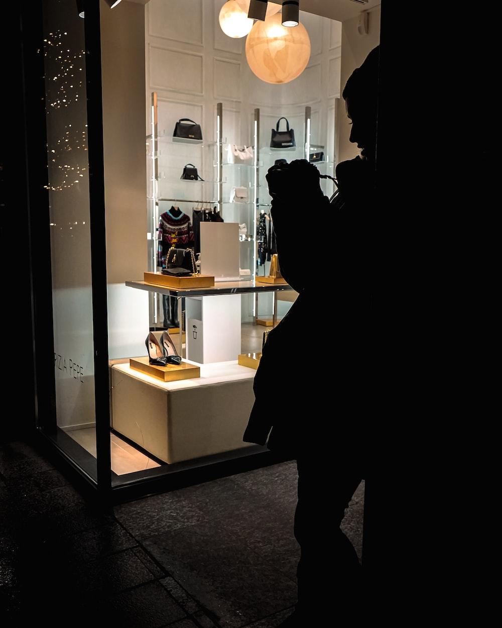 person in black coat standing in front of mirror