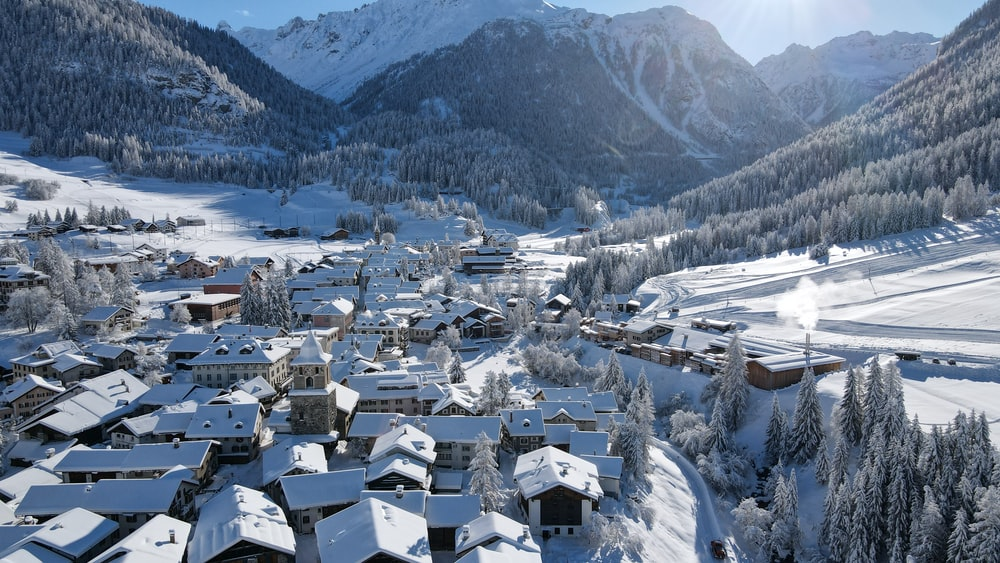 white houses on snow covered ground near mountains during daytime
